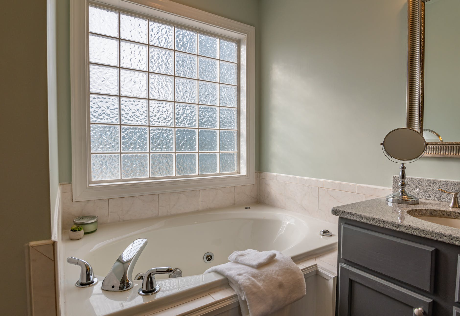 A large bath next to a window and sink
